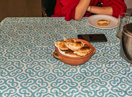 woman eating empanadas, typical dish from Argentina, artisan ceramic pot with similar original indigenous pottery with fresh homemade empanadas (detailed close-up; selective focus)
