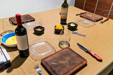 Family house table prepared to celebrate the gathering of friends, with sauces, cheese, wine and dishes.