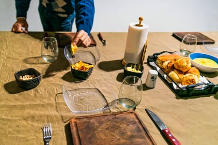 man holding french fries at a family home table prepared to celebrate the gathering of friends, with sauces, cheese, wine and dishes. Reklamní fotografie
