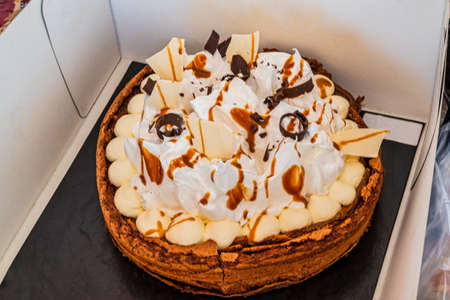 Homemade cake with dulce de Leche, salt caramel, cream, chocolate and meringues. Close up. Focus selective.