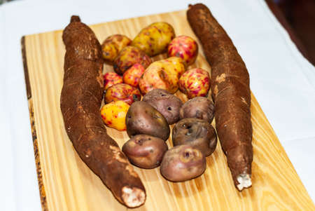 Raw yucca on the wooden table, Manihot esculenta. (Cassava raw tuber) with regional potatoes from the Andes at a market in Peru, Bolivia, Argentina, south america.