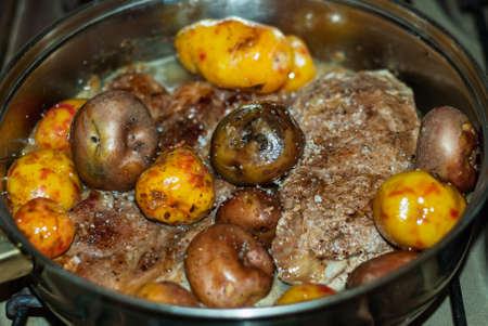 Beef steaks cooked to the pan with onions, Andean potatoes, fine herbs and spices. Reklamní fotografie