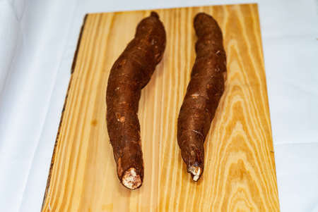 Raw yucca on the wooden table, Manihot esculenta. (Cassava raw tuber). Cassava, also called mandioca, yuca, balinghoy, mogo, mandioca, kamoteng kahoy, tapioca and tapioca root. Focus selective.