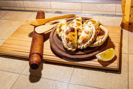 Wooden table with fresh homemade Empanadas (detailed close-up shot; selective focus)