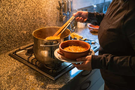woman serving locro, typical Argentine food on handmade ceramic plates.