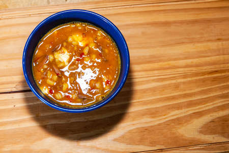 Locro, typical and traditional Argentine food served in a blue container on a wooden board, accompanied by bread and a glass of wine, with spoons. Selective focus. Reklamní fotografie