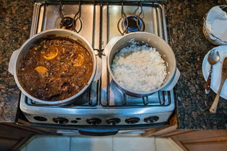 Typical Brazilian dish called Feijoada. Made with black beans, pork and sausage. Served on a white plate during a meeting. Imagens