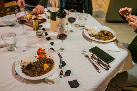 Typical Brazilian dish called Feijoada. Made with black beans, pork and sausage. Served on a white plate during a meeting.