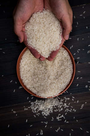 Closeup raw glutinous rice in hand of man, Organic white sticky rice