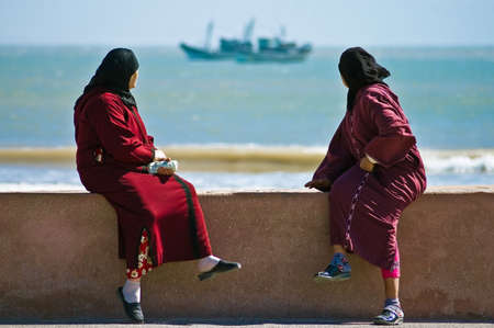 2 womens watch the horizon while they rest at Essaouiras seafront, located on the Atlantic coast of Marrakechs province on western Morocco.