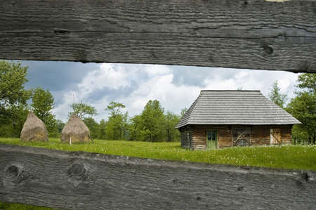 Besides every road along the Maramures province, at the north of Romania, we can find these farmer houses, guarded by hay piles. Stock Photo