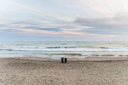 Two trash cans on the beach with a cloudy day photo
