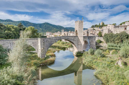 Medieval bridge across Fluvia river in Besalu, Spain Фото со стока