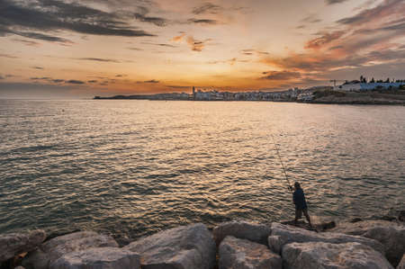 Fisherman and sunset on Sitges village on southern Barcelona in Catalonia Province, Spain photo