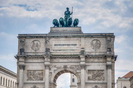 The Victory Gate (Siegestor), a three-arched triumphal arch crowned with a statue of Bavaria with a lion-quadriga in Munich, Germany photo