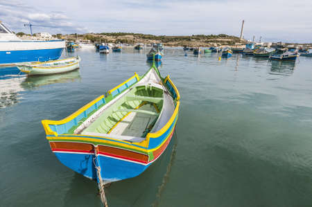 Traditional Kajjik Boat at Marsaxlokk harbor, a fishing village located in the south-eastern part of Malta. photo