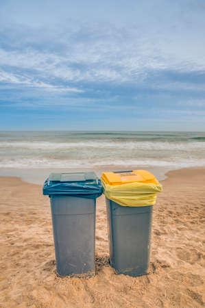 botes de basura: Dos botes de basura en la playa con un d�a nublado Foto de archivo
