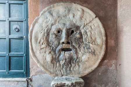 The Mouth of Truth (La Bocca della Verità) carved from Pavonazzo marble, in the portico of the church of Santa Maria in Cosmedin in Rome, Italy.
