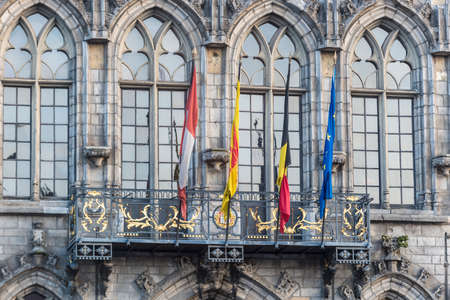 walloon: Flags waving on City Hall building facade in Mons, capital of the Wallonian province of Hainaut in Belgium.