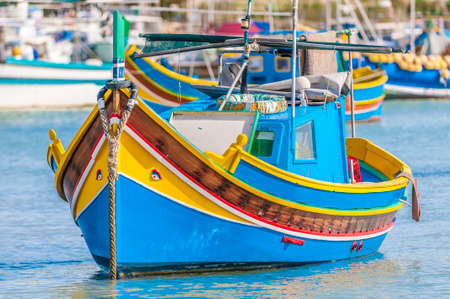 Traditional Luzzu boat at Marsaxlokk harbor, a fishing village located in the south-eastern part of Malta. photo