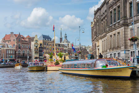 navigating: AMSTERDAM, NETHERLANDS – JUNE 16, 2013: One of the thousands boats navigating along the famous Amsterdam canals.