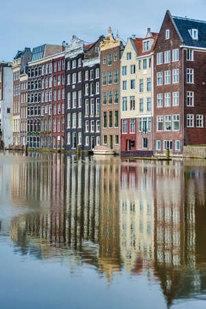 dam square: The Damrak canal, running between Amsterdam Centraal in the north and Dam Square in the south in Amsterdam, Netherlands.
