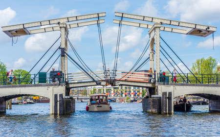 drawbridge: AMSTERDAM, NETHERLANDS – JUNE 16, 2013: Closed white drawbridge in Amsterdam, Netherlands.