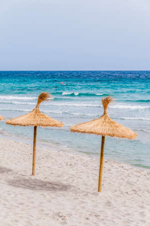 turism: Straw umbrellas on sand beach and clear sky. Stock Photo