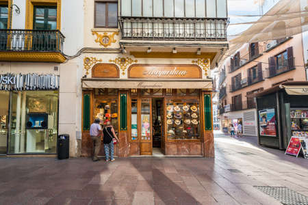 SEVILLE, ES - JULY 26, 2017: Maquedano Millinery on the street Sierpes, traditional and busy shopping street in the Spanish city of Seville, Andalusia, Spain. Editorial