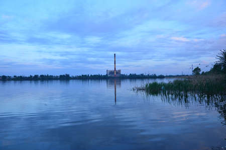 vespers: reflection of a waste incineration plant in the lake Stock Photo