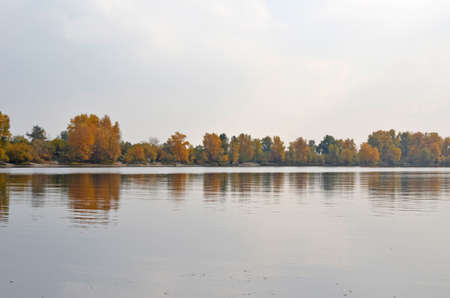 Gloomy scenery in the lakeside - photo of lake with autumn trees reflection Stock Photo