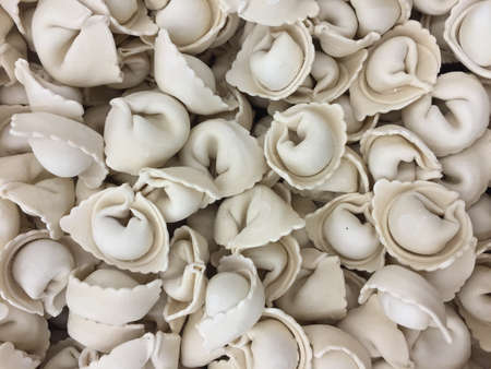 semimanufactures: Variety of fresh frozen dumplings ready for cooking pelmeni background