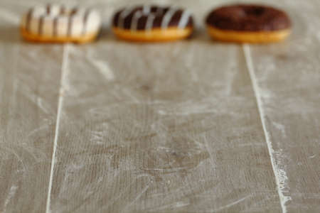 smudgy: three chocolate Donuts blurred background wooden table Stock Photo