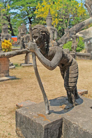 Statue traveler who leaned on his staff Laos, Buddha Park photo