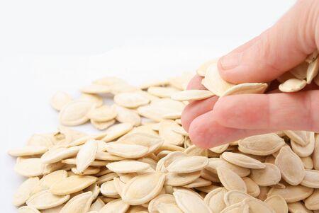 pumpkin seeds: Pumpkin seeds in hand on white background Stock Photo