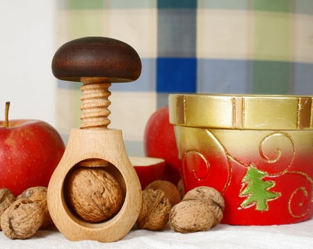 traditional wooden nutcracker, nuts, christmas bowl and apples photo