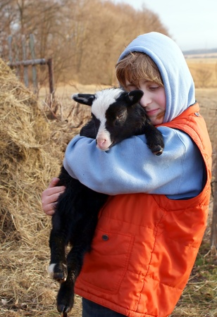 teenage boy with cute black lamb  photo