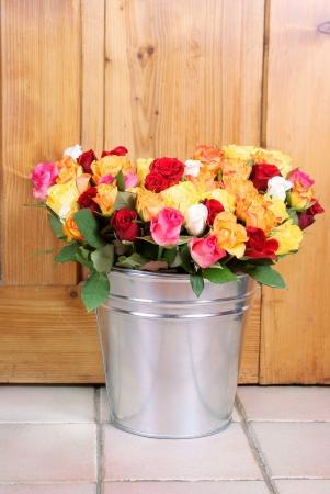 rosas naranjas: ramo de rosas en balde metálico en un fondo de madera
