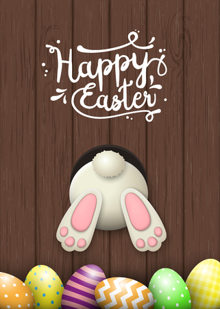 brown egg: Easter motive, white bunny bottom and easter eggson dark brown wooden background with text Happy Easter