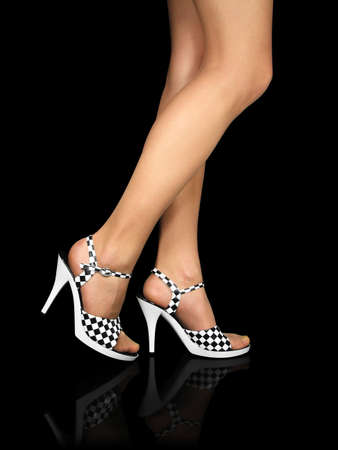 Sexy legs with high heels shoes reflecting in the mirror floor. Isolated on black background. Contains clipping path.