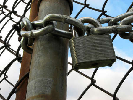 Lock and chain on an iron gate, and sky seen through the chain link fence. photo