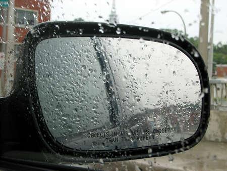 Rainy day: raindrops on a car window and rear mirror. Stock Photo - 719604