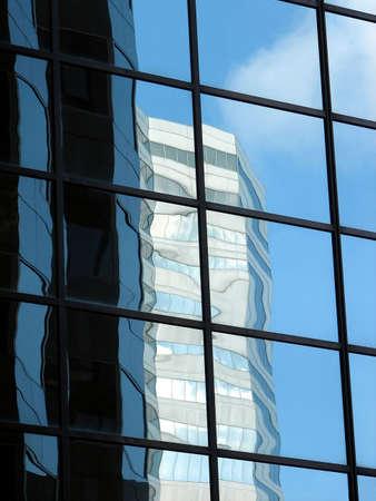 edificio corporativo: Con ventanas de vidrio de las empresas de construcci�n que refleja otra torre de oficinas y el cielo azul.  Foto de archivo
