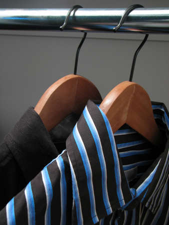 Two shirts of different colors on wooden hangers in a closet. photo
