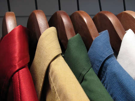 Colourful shirts on wooden hangers Stock Photo