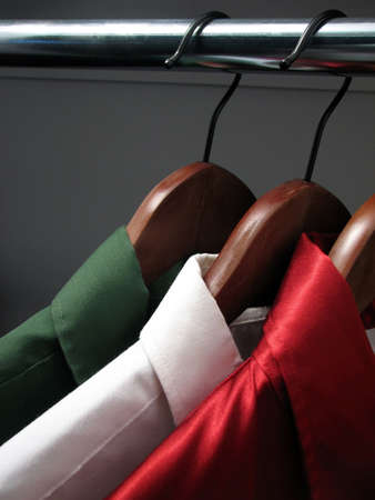 Shirts representing Italian flag. Colors of Italy: green, white and red shirts on wooden hangers in a closet. Stock Photo - 719763