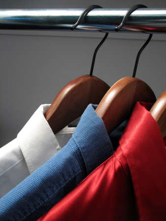 hangers: Shirts representing Russian flag. Colors of Russia: white, blue and red shirts on wooden hangers. Stock Photo