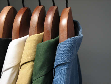 Shirts of different colors on wooden hangers in a closet.