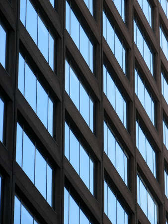 reflects: Glass-windowed corporate building reflects the blue sky.