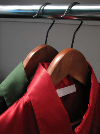closet: Stylish green and red shirts with an empty label, on wooden hangers in a closet. Stock Photo